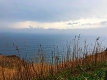 Meer und Herbstrasenfläche mit Wolke Stockfotos