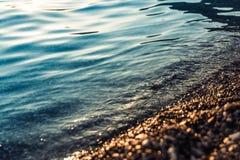 Meer und Kiesel bei Sonnenuntergang stockbilder