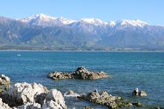Meer und Schnee bedeckten Berge, Kaikoura, NZ mit einer Kappe Stockbild