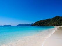 Meer und weißer Sand mit klarem blauem Himmel Lizenzfreies Stockbild
