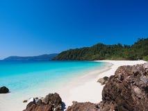 Meer und weißer Sand setzen mit klarem blauem Himmel auf den Strand Lizenzfreies Stockbild