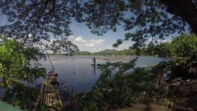 Meerbewoners die karweien, één wasgroenten met meerwater doen, één het paddelen boot van het bamboevlot stock video