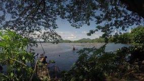 Meerbewoners die karweien, één wasgroenten met meerwater doen, één het paddelen boot van het bamboevlot stock footage