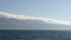 Meerblick auf den Bergen bedeckt mit Wolken Lizenzfreie Stockfotos