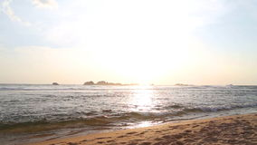 Meerblick in Hikkaduwa im Sonnenuntergang mit den Wellen, die den Strand spritzen stock footage