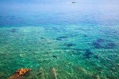 Meerblick mit blauem Wasser, Steinen und Schiff Felsiges Seeufer Blauer Himmel und bunter Strandregenschirm Lizenzfreies Stockbild