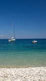 Meerblick mit blauer Staffelung und verankertem Segelboot Lizenzfreie Stockfotos