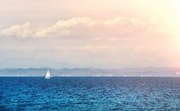 Meerblick mit einem einzigen weißen Segelboot im Abstand Stockbild