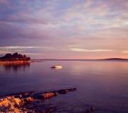 Meerblick mit einsamem Boot im Meer bei Sonnenuntergang Stockfotografie
