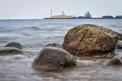 Meerblick mit Steinen und Booten am Pier im Hintergrund Stockfotografie