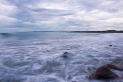 Meerblickvertretung bewegt wellenartig, einen Nebel bildend, während sie gegen Küstenfelsen bei Plum Point, Jamaika spritzen lizenzfreies stockfoto