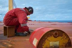 An meeres- circa im Oktober 2018: Seeleute, die alte D-Clips an der offenen Plattform eines Schiffs schneiden SchiffsWartungskonz lizenzfreie stockfotografie