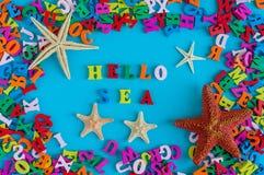 Meeres- Wort bestanden aus kleinen farbigen Buchstaben Starfish auf einem Hintergrund der bunten Türkisblautabelle Seashells gest stockbilder