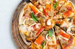 Meeresfrüchte-italienische Pizzascheibe auf hölzernem Teller Stockfoto