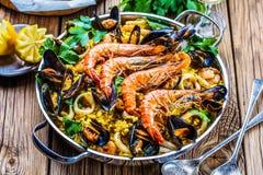 Meeresfrüchte-Paella im Mann auf einer weißen Tabelle mit Dekoration stockfotografie