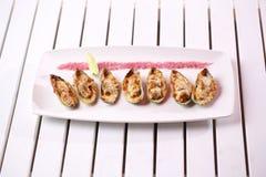 Meeresfrüchte Schalentiermiesmuscheln Gebackene Miesmuscheln mit Käse, Koriander und Zitrone in den Oberteilen Stockfotografie
