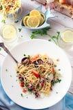 Meeresfrüchte-Spaghettis auf einer weißen Tabelle mit Gläsern Zitronen-Wasser Lizenzfreies Stockbild