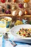 Meeresfrüchte-Spaghettis auf einer weißen Tabelle mit Muschel-Hintergrund Lizenzfreie Stockfotos