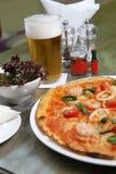 Meeresfrüchtepizza mit Salat und Bier lizenzfreie stockfotografie