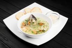 Meeresfrüchtesuppe mit Garnelen und Miesmuscheln in einer Schüssel auf dem schwarzen hölzernen Hintergrund Stockfotos