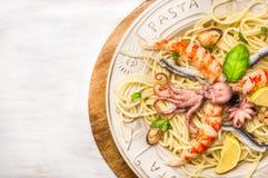Meeresfrüchtespaghettis mit ganzer Babykrake und großer Garnele in der Platte, Abschluss oben Lizenzfreies Stockfoto