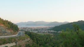 Meereslandschaft mit Bergsilhouetten auf Skyline-Hintergrund Autostraße im Bergtal auf Meer und grünen Hügeln stock video footage