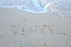 Meereswellen auf dem sauberen Strand mit einem Wort der Liebe auf dem Sand stockfotografie