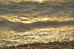 Meereswellen auf dem Schindel setzen bei dem Sonnenuntergang auf den Strand Lizenzfreie Stockfotos