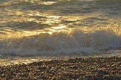 Meereswellen auf dem Schindel setzen bei dem Sonnenuntergang auf den Strand Stockfotos