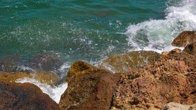 Meereswellen, die über große Steine auf Draufsicht des Ufers spritzen stock footage