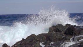 Meereswellen, die über Steinen an der felsigen Küste mit Spray in der Zeitlupe spritzen stock video