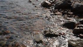 Meereswellen, die auf dem Steinstrand zusammenstoßen stock video footage