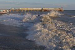 Meereswellen, die auf dem Ufer der Erholungsortregelung Adler auf dem Hintergrund des Piers in der untergehenden Sonne brechen Lizenzfreie Stockfotografie