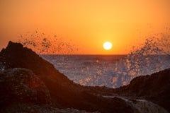 Meereswellen, die auf den Felsen auf einem tropischen Strand, im schönen warmen Sonnenunterganglicht zerquetschen und spritzen lizenzfreie stockfotos