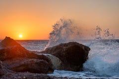 Meereswellen, die auf den Felsen auf einem tropischen Strand, im schönen warmen Sonnenunterganglicht zerquetschen und spritzen stockfotografie