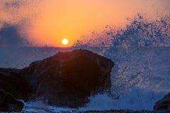 Meereswellen, die auf den Felsen auf einem tropischen Strand, im schönen warmen Sonnenunterganglicht zerquetschen und spritzen stockfoto