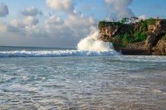 Meereswellen, die an den Felsen in Bali, grüne üppige Natur umgibt das schöne Meerwasser im Indischen Ozean spritzen lizenzfreie stockbilder