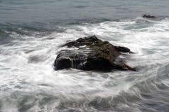 Meereswellen die Uferfelsen schlagend lizenzfreie stockfotografie
