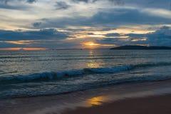 Meereswellen rollen auf einem sandigen Strand am Abend während eines beautifu Stockbild