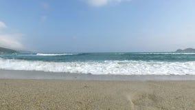 Meereswellen stoßen über dem Sandstrand am unny Tag zusammen stock video footage