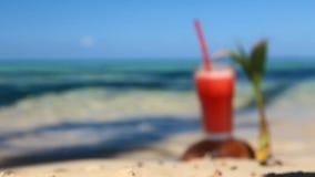 Meereswellen waschen ein Glas Saft mit Kokosnuss stock footage