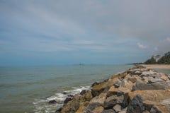 Meereswellenwimpernansatz-Auswirkungsfelsen auf dem Strand unter blauem Himmel Stockbild