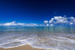 Meereswellenwimpernansatz-Auswirkungsfelsen auf dem Strand unter blauem Himmel Stockfoto