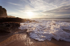 Meereswoge mit Schaumschlagen gegen die Felsen bei Sonnenuntergang Stockfoto