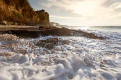 Meereswoge mit Schaumschlagen gegen die Felsen bei Sonnenuntergang Stockfotos