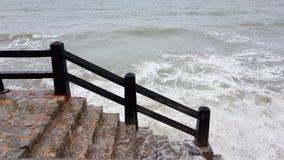 Meereswoge schlägt das Ufer mit einer Steintreppe Stockfoto