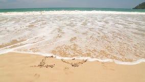 Meereswogebedeckung fasst ich liebe dich geschrieben in Sand auf Strand ab stock footage
