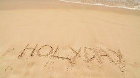 Meereswogebedeckungs-Wortfeiertag geschrieben in Sand auf Strand stock video
