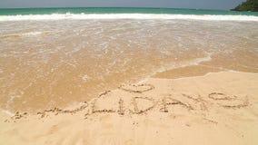 Meereswogebedeckungs-Wortfeiertage geschrieben in Sand auf Strand stock footage
