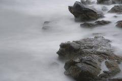 Meereswogen über Felsen bei Cliff Walk in Rhode Island Stockfotos